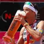 Andreas Raelert de Alemania, después de ganar el triatlón Challenge-Roth en Julio 2014 bebiendo un vaso de cerveza